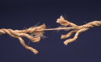 Frayed rope about to break isolated on blue background