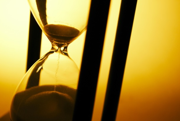 Conceptual image of measuring passing time with a close up view of sand running through an hourglass or egg timer on a golden background with copyspace